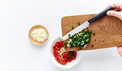 Do pokrojonych pomidorów dodajemy czosnek, dymkę i starty ser